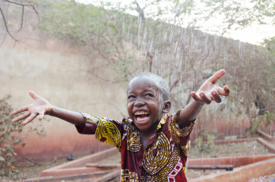 sweet little african boy under the rain